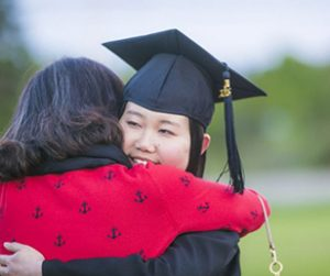 Student Graduating and being hugged.